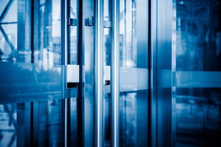 building entrance: detail of office building entrance,blue toned image.