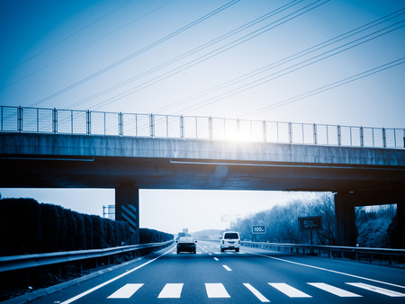 overbridge: car driving on the highway,blue toned image. Stock Photo