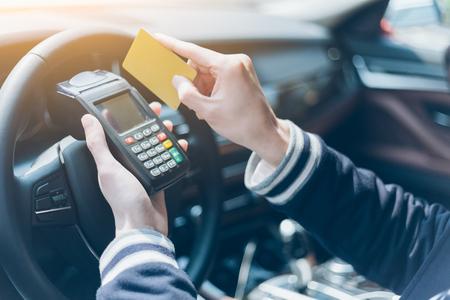 uomo in una carta di credito auto strisciata sulla macchina POS wireless Archivio Fotografico