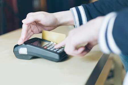 enters: Male enters PIN code on wireless POS machine with hand covering