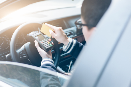cardreader: man in a car swiping credit card on wireless POS machine