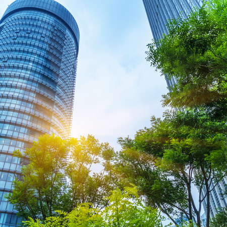 low angle views: modern office building with green trees Editorial