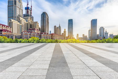 empty pavement and city skyline under blue sky Stockfoto