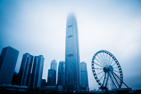 observation wheel and Two International Finance Center,Hong Kong,china,asia,blue toned. Stock Photo