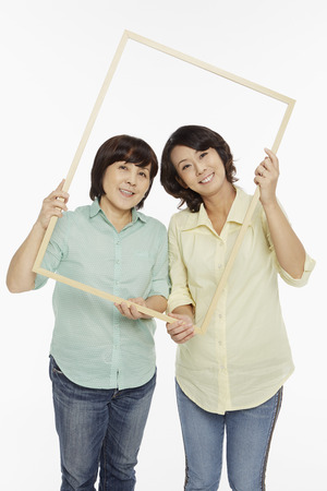 Women holding up a wooden picture frame