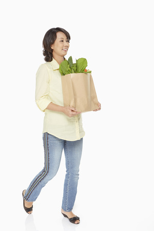 Woman carrying a bag of groceries 写真素材