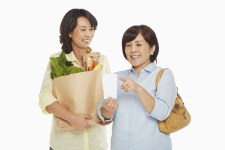Women with groceries checking their shopping list photo