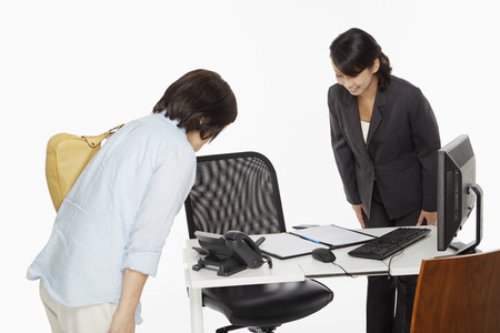 courteous: Two women bowing, facing each other