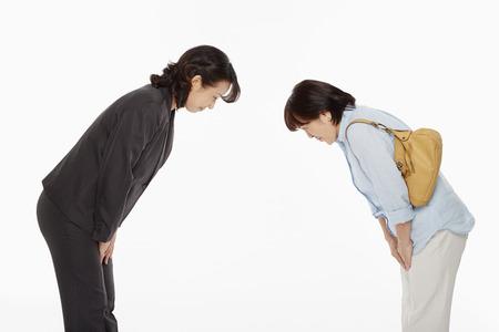 Twee vrouwen buigen, tegenover elkaar Stockfoto