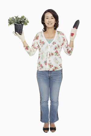 Woman holding up a potted plant and a spade