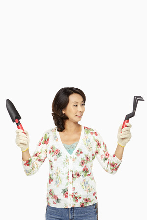 Woman holding up a spade and a garden fork