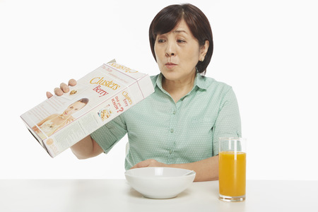 cereal box: Woman looking into an empty cereal box Stock Photo