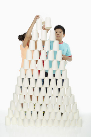 Boy and girl stacking up disposable cups together Stock Photo