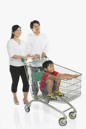 Parents pushing a shopping cart with son in tow photo