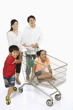 Parents pushing a shopping cart with children in tow photo