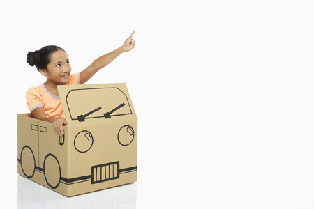 Girl in cardboard bus showing hand gesture photo