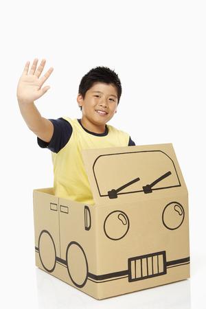 cardboard only: Boy sitting in a cardboard bus, waving