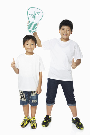 Boy holding up a cut out light bulb over another boys head