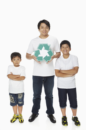 recycle logo: Father holding up a Recycle logo while sons stand with arms crossed