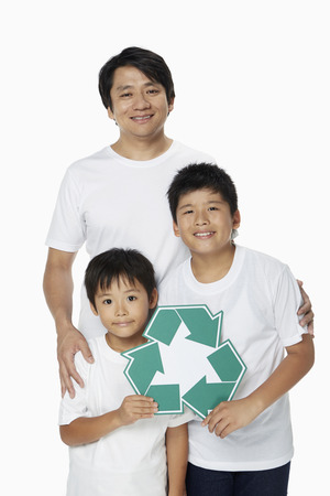 recycle logo: Family of three smiling and holding up a Recycle logo