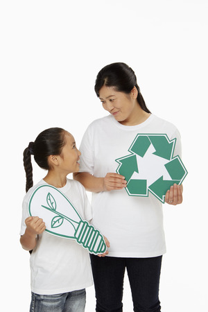 recycle logo: Mother and daughter holding up a Recycle logo as well as a cut out light bulb Stock Photo