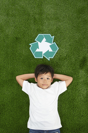 Boy lying on the grass, smiling photo