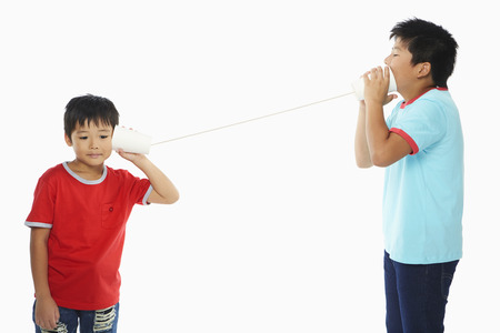 Two boys playing with a paper cup phone