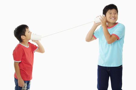 Two boys playing with a paper cup phone photo