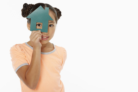 Girl looking through a cut out house Stock Photo