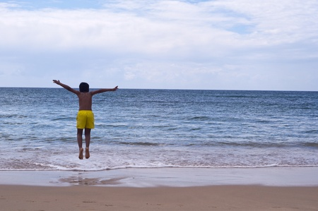 child jumping on beach with blue sky in the background photo