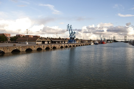 harbor with boats, cranes and a bridge in the background photo