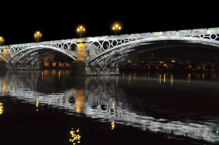 seville: triana bridge at night in seville, spain