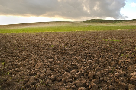 brown soil of cultivated field with hills and cloudy sky as background photo