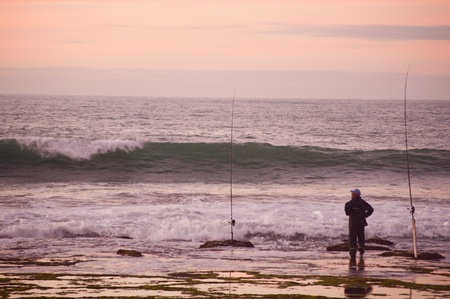 fishingpole: Fisheman with fishing rod on the beach,
