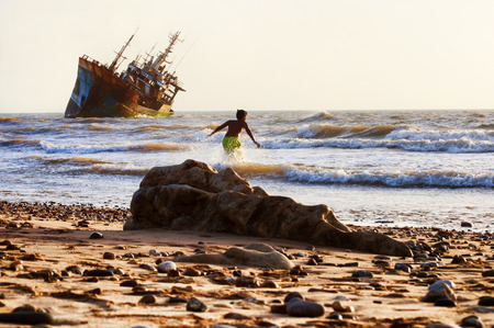 playa: ship-wreck in  la playa beach with child playing on beach, western sahara.