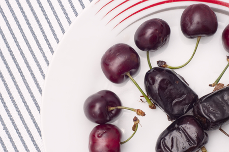 dates and cherries isolated on white