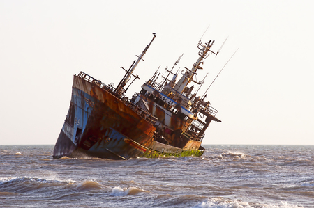 Abandoned broken ship-wreck beached on rocky ocean , western sahara coast Stock Photo