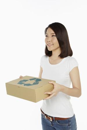 reciclable: Mujer alegre con una caja de cart�n reciclable Foto de archivo