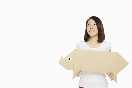 Woman holding up a paper pig photo