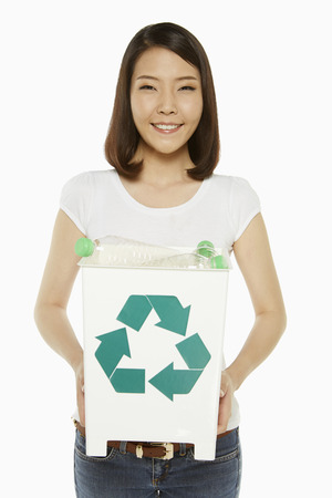 Woman holding up a recycling bin filled with plastic bottles photo