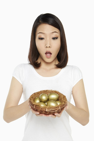 Woman holding a nest filled with gold eggs, looking shocked photo