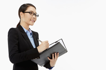 Businesswoman writing notes in her folder photo