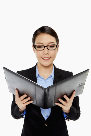 Cheerful businesswoman reading notes from a folder photo