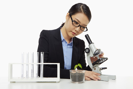 Businesswoman looking through a microscope photo