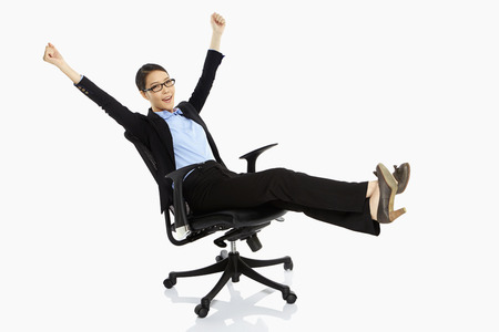 relieved: Businesswoman resting on a chair, cheering