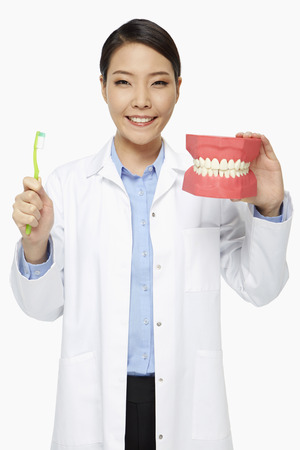Medical personnel holding up a tooth brush and a set of dentures photo