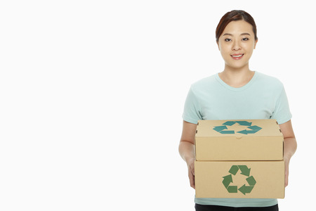 Woman carrying a stack of recyclable cardboard boxes photo