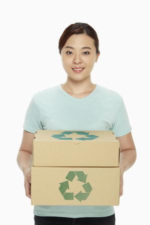 reciclable: Mujer que lleva una pila de cajas de cart?n reciclables