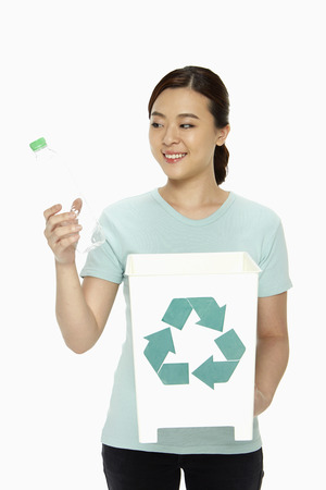 Woman with a plastic bottle and a recycling bin photo