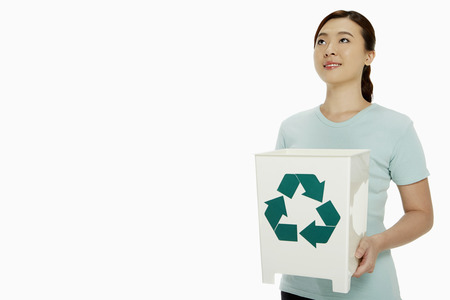 Woman holding up a recycling bin photo